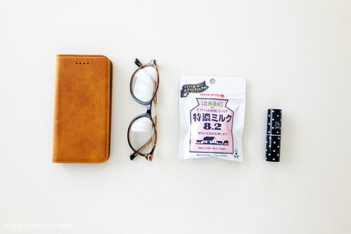 スマホ、眼鏡、ミニパックのキャンディ、リップが並ぶ画像