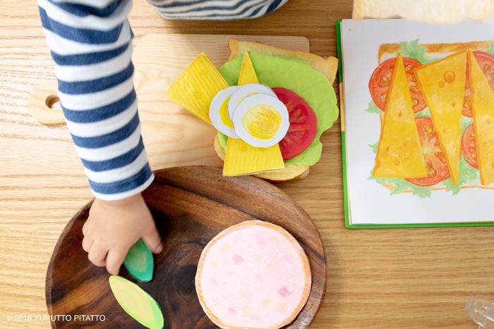 サンドイッチのおもちゃで遊ぶ子どもの手