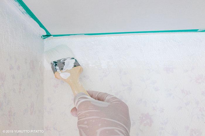 刷毛で壁にペンキを塗る