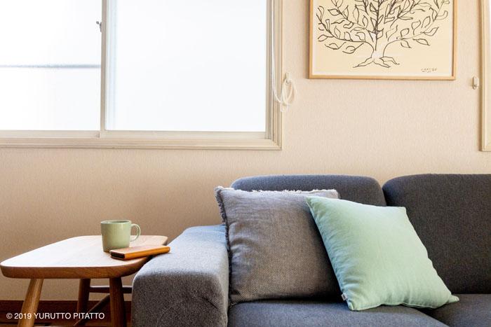 グレーのソファーとクッションとアート