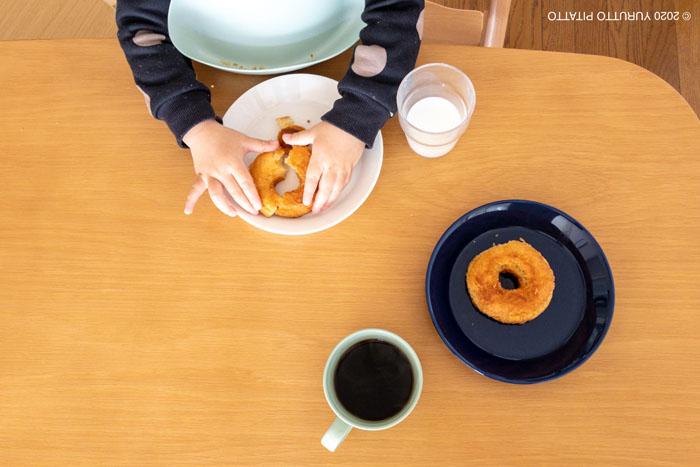 ドーナツを持つ子ども。ティーマのプレートとマグ。