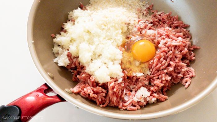 フライパンに卵、ひき肉、パン粉などハンバーグの材料を入れる