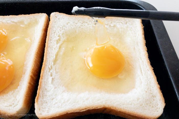 食パンにのせた生卵の白身をきる