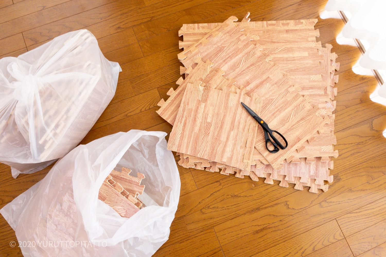 木目調ジョイントマットをはさみで切ってゴミ袋へ